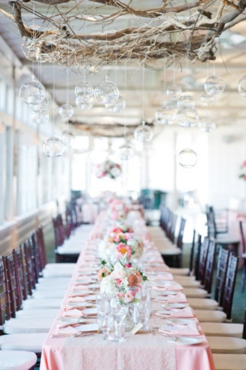 an ethereal indoor wedding reception with a vine chandelier with glass bubbles and ombre tablecloths in pink plus pink flower centerpieces