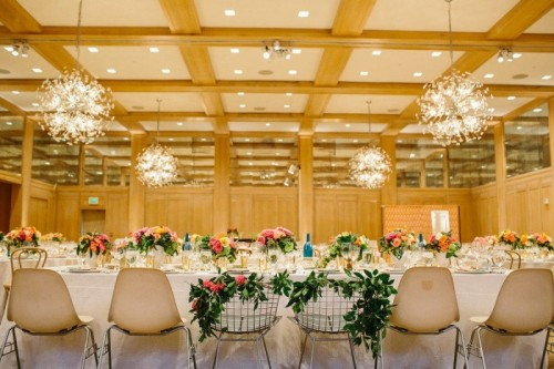 a spring wedding reception with greenery on the chairs and bright florals on the tables plus pendant lamps