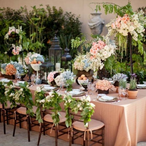 a lush outdoor spring wedding reception with lots of lush greenery, pastel blooms and tall candle holders