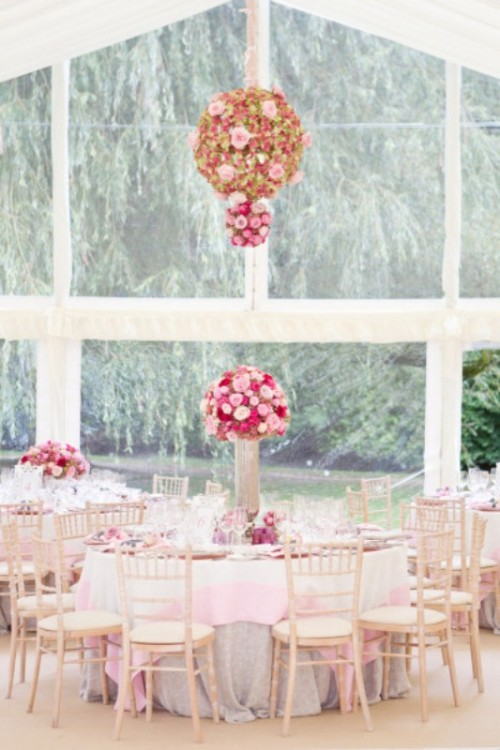 a chic indoor spring wedding reception with lush bright blooms over the tables and on them, pink tablecloths and pastel touches