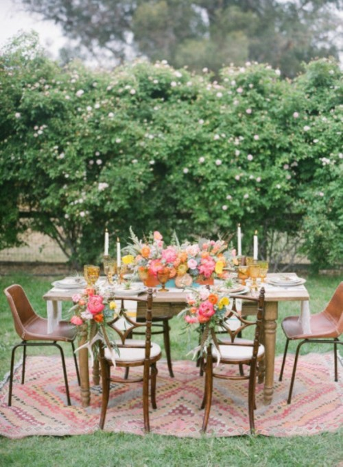 a bright outdoor spring wedding reception with colorful blooms, glasses and a boho rug under the table