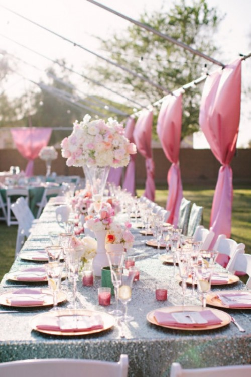 a colorful outdoor spring wedding reception with pink curtains, napkins, candleholders and tall centerpieces of blush blooms