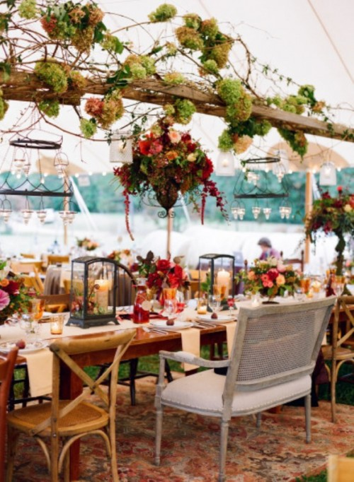 a super lush outdoor-indoor spring wedding reception with lots of candle chandeliers, greenery, moss and bright blooms for a woodland feel