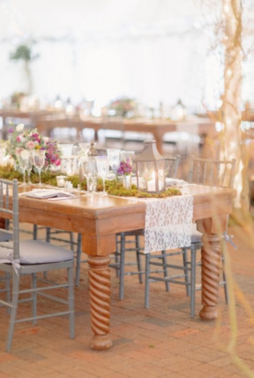a cozy and casual spring wedding reception with lace table runners, moss, bright flowers and candle lanterns