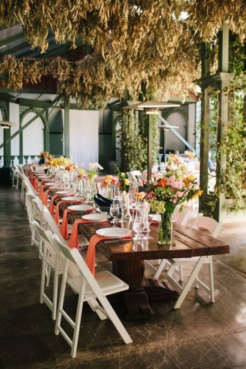 an indoor spring wedding reception with greenery over it, bright blooms and greenery, peachy napkins