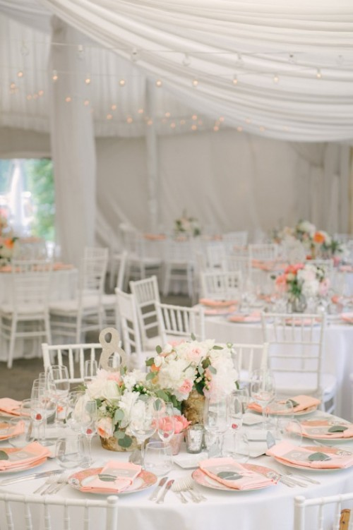 an indoor spring wedding reception in white, with pastel blooms and greenery, peachy chargers and monograms