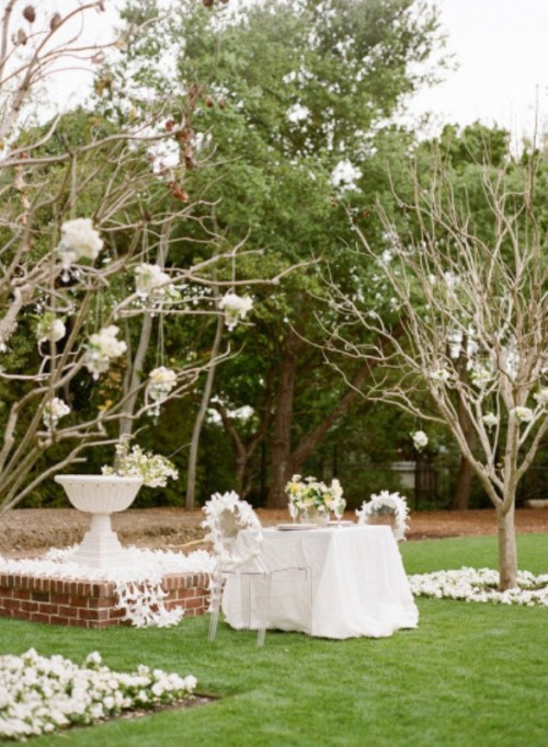 neutral and blooming spring reception space done with whte blooms on branches, blooms on the ground and blooms on the chairs