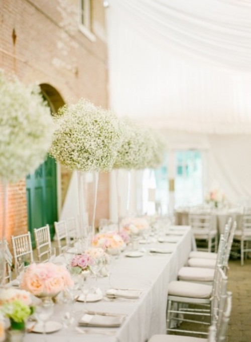 a romantic indoor spring wedding reception with tall baby's breath centerpieces, pastel blooms and white linens
