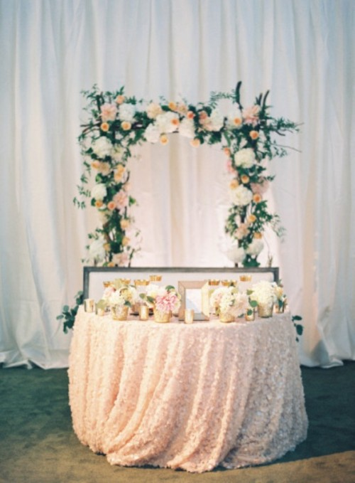 blush and white blooms, candles in candleholders and a lush floral arch of neutral blooms and greenery