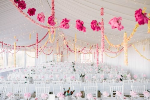 an indoor spring wedding reception with pastel and white bloom garlands hanging down, pink blooms on the tables and all white everything