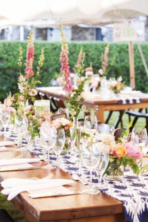 a casual outdoor spring wedding reception with printed blue table runners, pink blooms and greenery on the tables
