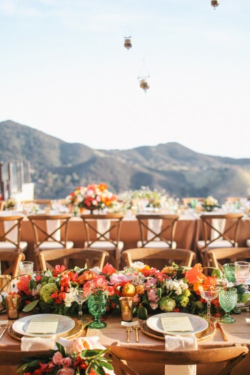 a colorful outdoor wedding reception done with bold blooms and greenery, some candles and colorful glasses