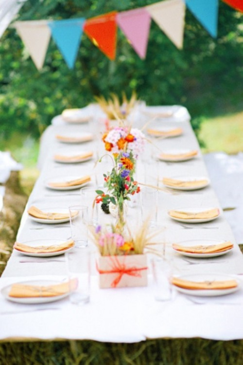 a colorful outdoor spring wedding reception with colorful buntings, bright blooms, neutral linens and a white base