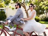 a retro-inspired ruffle knee wedding dress with a bright yellow sash and sunglasses for a cool bridal look