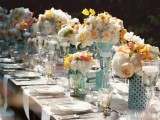 an aqua blue, white and yellow wedding tablescape with lush florals for a retro wedding
