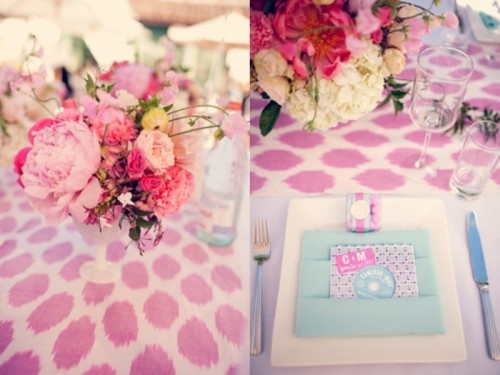 a pink and light blue wedding tablescape with lush florals, a napkin pocket and a bright printed tablecloth