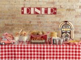 a cool cookies, pancakes and sweets station done in red and white, with a plaid tablecloth, a toy retro car