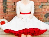a retro midi wedding dress with a red sash and red underskirt, red shoes and pearls plus a birdcage veil