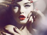 a retro-inspired makeup with cat eyes eyeliner, deep red lips and wavy updo for a retro bride