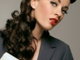 a retro-inspired hairstyle with a sleek bump and long wavy ponytail plus a white hair tie