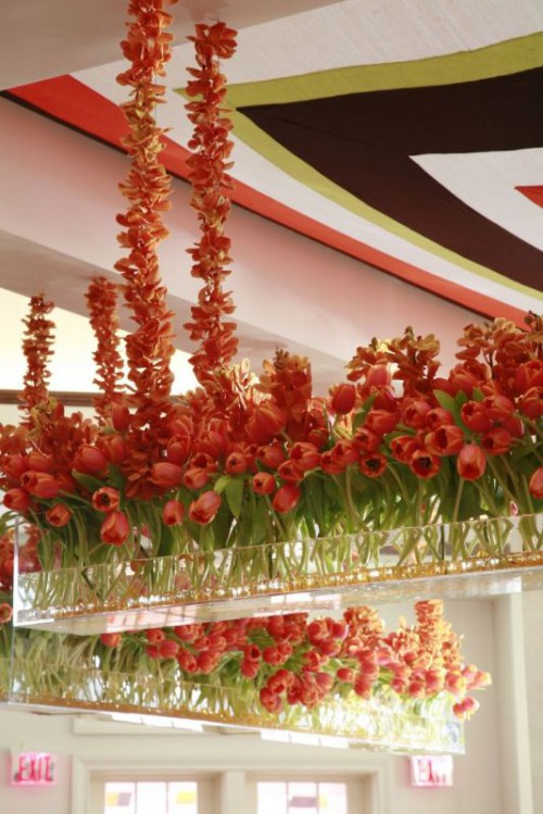lush overhead decor of red tulips in acrylic boxes and their petals coverign the ropes on which the installation is hanging
