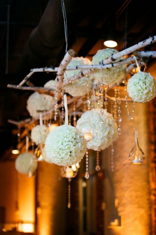 an overhead floral installation of brich branches, crystals hanging down, clear candleholders and some white floral orbs is wow