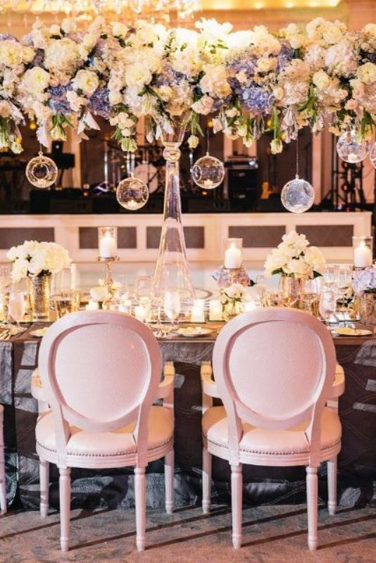 a neutral and pastel overhead floral decoration with some bulbs hanging down is romantic and beautiful