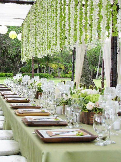 garlands of green and white blooms hanging down from overhead are a chic and cool idea to enliven your reception
