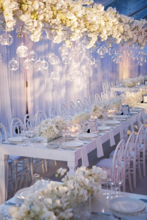 a lush white floral installation with candles hanging in clear candleholders from above