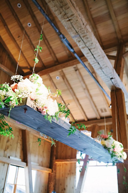 a simple rustic installation of a board and some neutral blooms and greenery for a cozy farmhouse reception