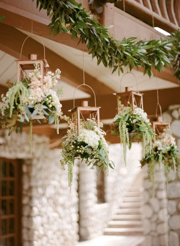 copper candle holders with white blooms and greenery plus a lush greenery garland over the reception