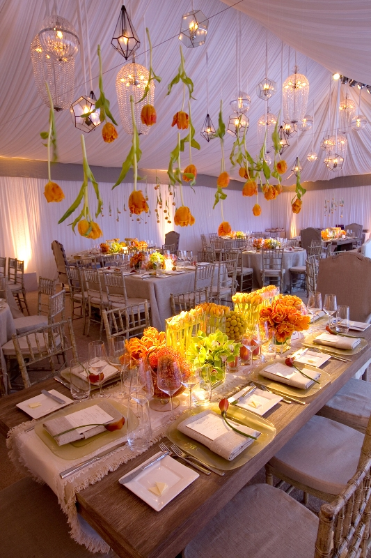 some orange tulips plus refined crystal chandeliers hanging down from above look super cool and chic