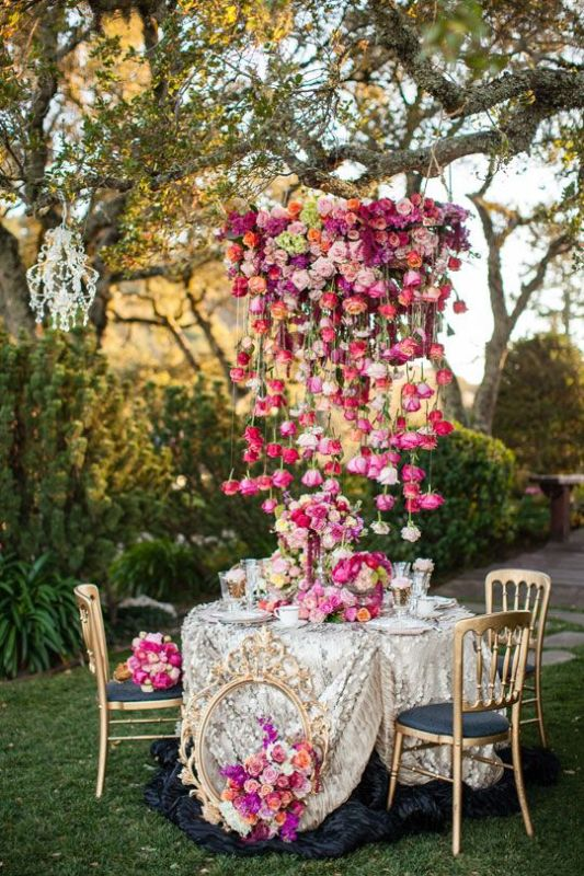 a bright and lush floral chandelier of bold red, pink, purple and blush blooms that touches the table and acts as a centerpiece, too