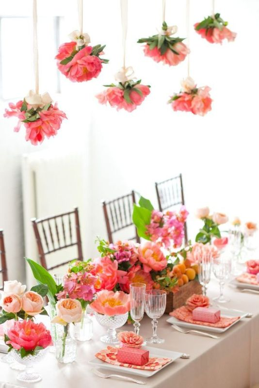some pink peonies hanging down from above echo with the centerpieces and look very cool
