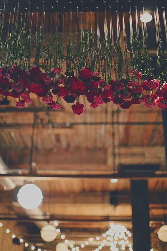 red carnations hanging down from overhead are a bright and chic idea to rock