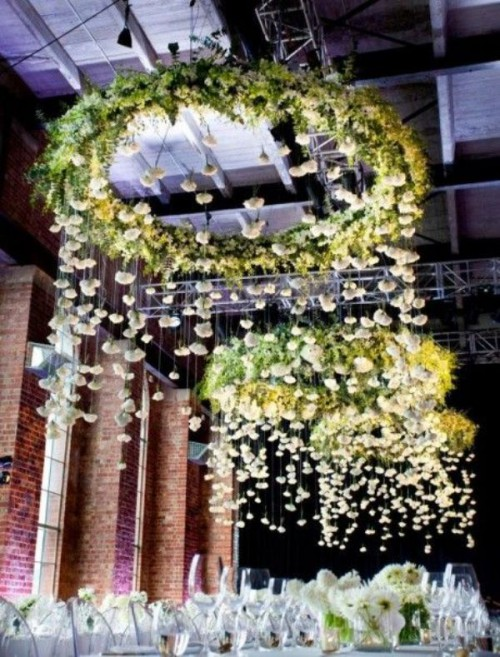 super lush and oversized green chandeliers with white blooms hanging down are an amazing reception decoration