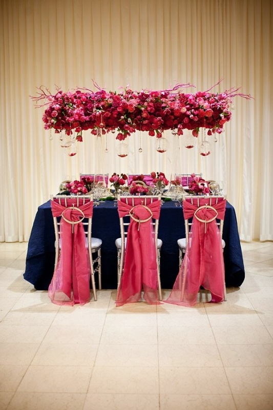a luxurious red and pink overhead pink decoration with bulbs and petals in them is a super bright touch to your reception