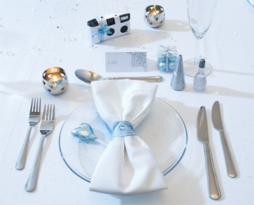 a beautiful silver and ice blue winter wedding place setting with a ice blue ornaments, an ice blue glass plate, ribbons and salt and pepper