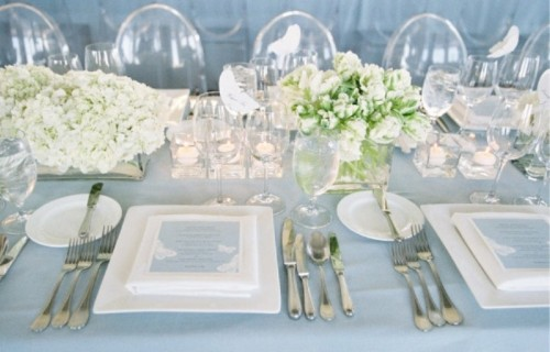 an ice blue and white winter wedding tablescape with ice blue cards and a tablecloth, white porcelain and white bloom arrangements