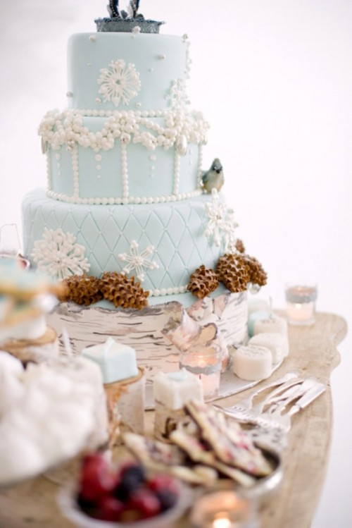a refined ice blue winter wedding cake with white patterns and pinecones, pearls and beads is a lovely and beautiful dessert