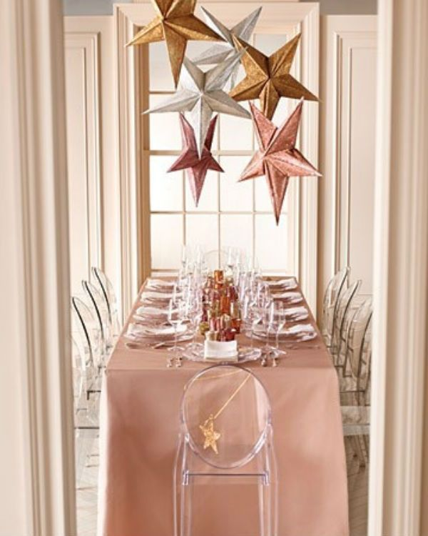 a pink tablecloth and gold, silver and rose gold stars over the table for decorating a cool glam wedding reception