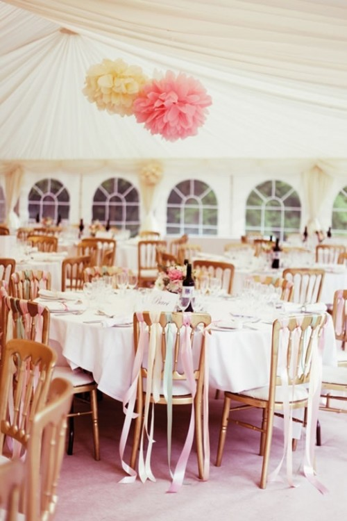 a white and pink paper pompom decoration and matching ribbons on the chairs for a romantic feel and a chic look