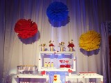 colorful paper pompoms over the dessert table accent it and add color to it making it fun
