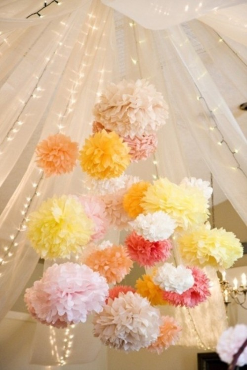 pastel-colored paper pompoms and lights under the dome make the reception space or dance floor fun and bold