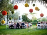 large colorful paper pompoms over the reception space make it bright, bold and cool
