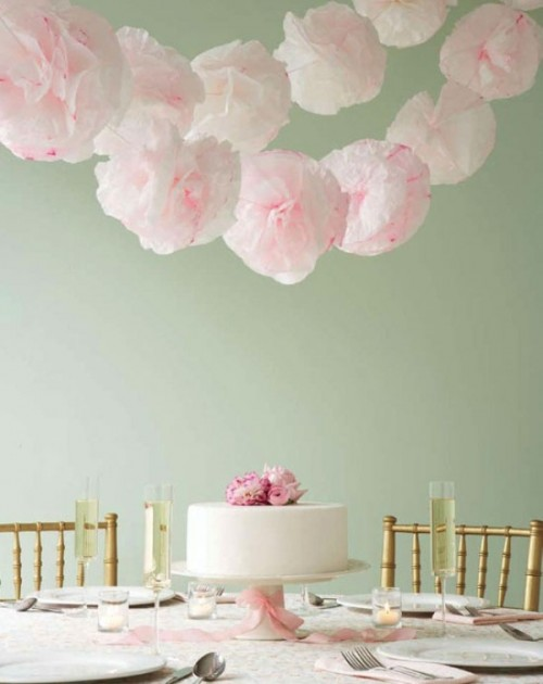 light pink paper pompom garlands over the table to match blusha nd light pink wedding decor and accent the tablescape