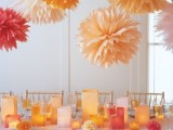 bright yellow, orange, red and white paper pompoms over the table match the square candle lanterns on the table and create a cohesive space