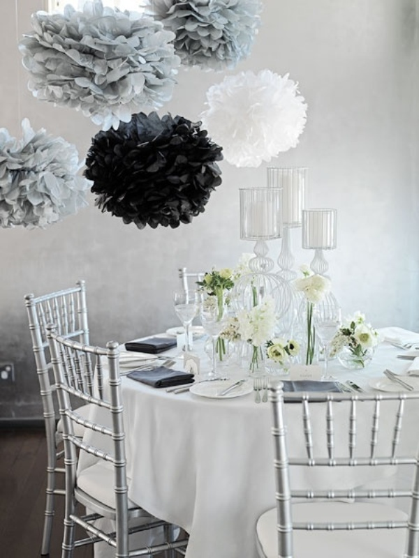 grey, white and black paper pompoms over the table perfectly finish the monochromatic space decor