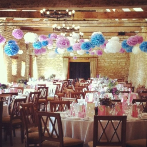 colorful blue, purple and white paper pompom garlands add color and fun to the barn wedding reception space