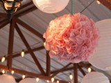 white paper lamps and pink paper pompoms plus lights for simple and cozy wedding reception decor